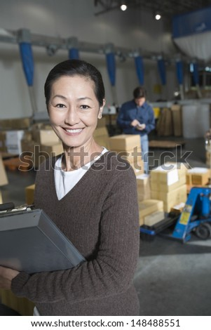 Portrait of a smiling Asian woman in distribution warehouse - stock photo