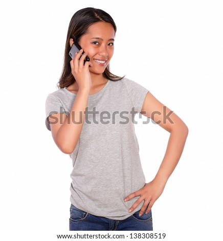 Portrait of a smiling asiatic young woman speaking on cellphone and looking at you on isolated background