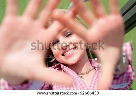 Portrait of a smiling attractive blond girl with open hands - stock photo