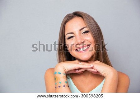 Portrait of a smiling attractive girl on gray background. Looking at camera - stock photo