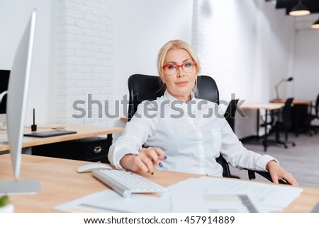 Portrait of a smiling attractive mature businesswoman using laptop in office - stock photo