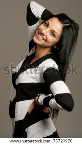 Portrait of a smiling attractive woman isolated on gray - stock photo