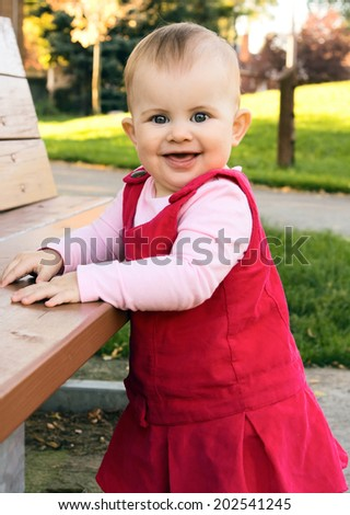 Portrait of a smiling baby girl in a pink dress standing near the bench and trying to make her first steps outdoor - stock photo
