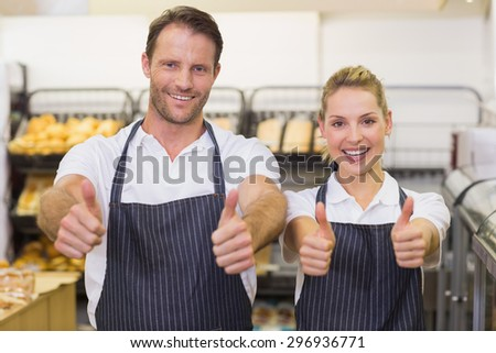 Portrait of a smiling bakers with thumb up in bakery - stock photo
