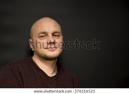 Portrait of a smiling bald man on a black background - stock photo