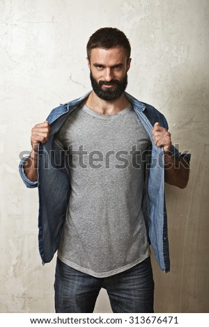 Portrait of a smiling bearded guy wearing grey t-shirt - stock photo