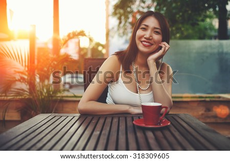Portrait of a smiling beautiful asian woman enjoying free time while sitting in coffee shop exterior terrace with beautiful sunset on background, wonderful young female posing for the camera in summer - stock photo