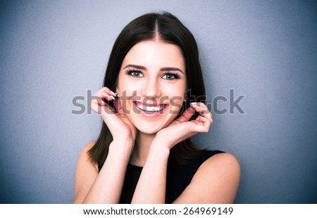 Portrait of a smiling beautiful woman touching her earrings over gray background. Looking at the camera - stock photo