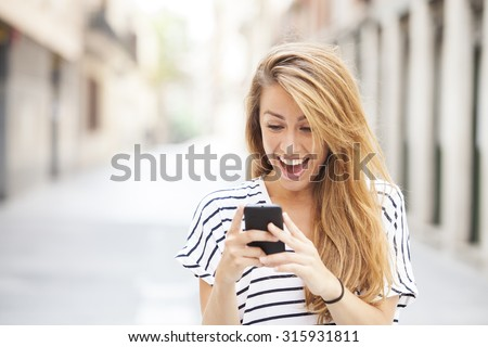 Portrait of a smiling beautiful woman typing on the smart phone with city unfocused background - stock photo