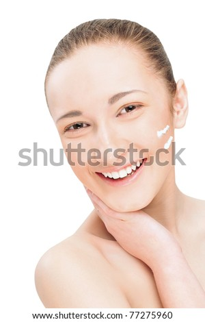 Portrait of a smiling beautiful young woman with two lines of cream on her face. Isolated white background. - stock photo