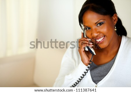 Portrait of a smiling black woman looking at you while talking on phone at home indoor. With copyspace