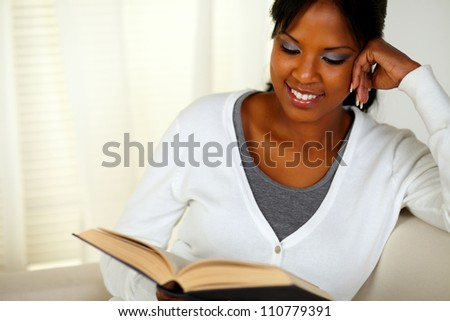 Portrait of a smiling black woman reading a book while sitting on sofa at home indoor
