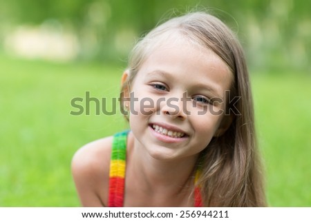 Portrait of a smiling blond girl. Girl seven years. - stock photo