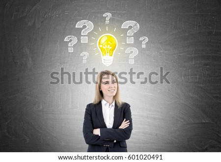 Portrait of a smiling blond woman standing with crossed arms near a blackboard with a yellow light bulb icon and question marks.