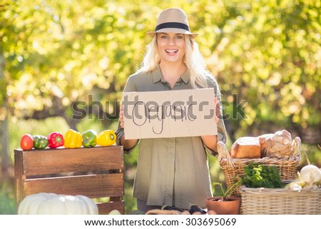 Portrait of a smiling blonde holding an organic signboard - stock photo