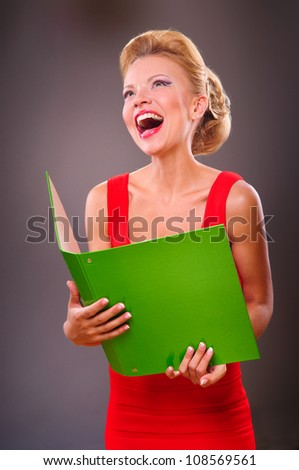 Portrait of a smiling blonde woman with the green folder in hands