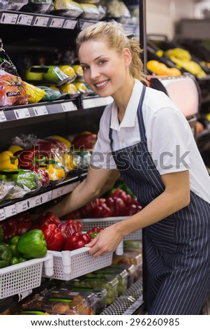 Portrait of a smiling blonde worker taking a vegetables in supermarket