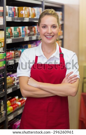 Portrait of a smiling blonde worker with arms crossed in supermarket
