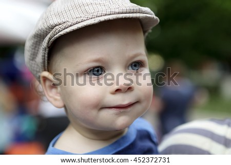 Portrait of a smiling boy in cap in summer park - stock photo