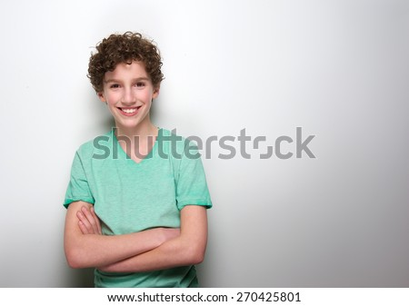 Portrait of a smiling boy with curly hair posing against white background - stock photo
