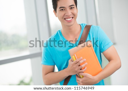 Portrait of a smiling boy with textbooks - stock photo