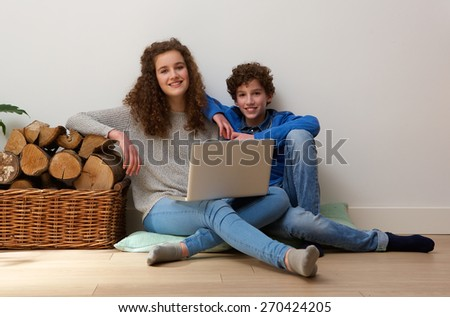 Portrait of a smiling brother and sister using laptop at home - stock photo