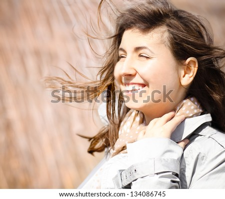 Portrait of a smiling brunette in windy day. Close up - stock photo