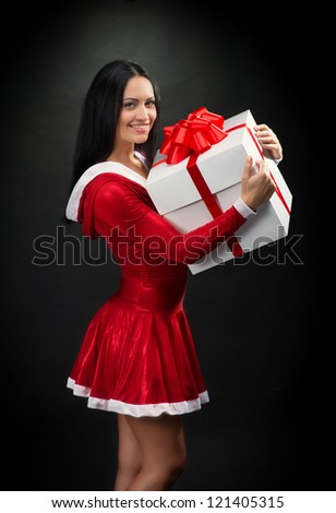 Portrait of a smiling brunette woman with Christmas present on dark background