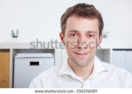Portrait of a smiling business man sitting in the office - stock photo
