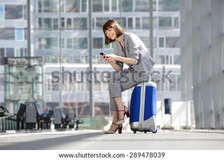Portrait of a smiling business woman looking at mobile phone and sitting on suitcase waiting at the airport - stock photo