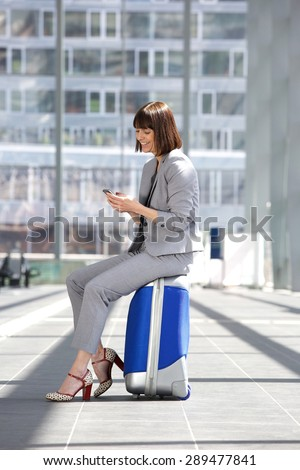 Portrait of a smiling business woman sitting on suitcase with mobile phone - stock photo