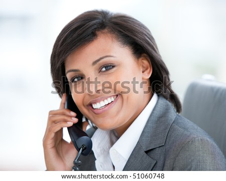 Portrait of a smiling business woman talking on phone in the office - stock photo