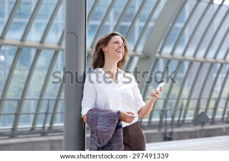 Portrait of a smiling business woman with mobile phone looking away - stock photo
