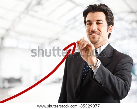 Portrait of a smiling businessman drawing a rising arrow, representing business growth