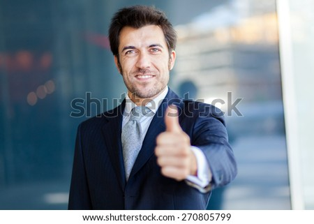 Portrait of a smiling businessman giving thumbs up - stock photo