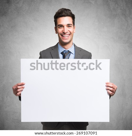 Portrait of a smiling businessman holding a white board - stock photo