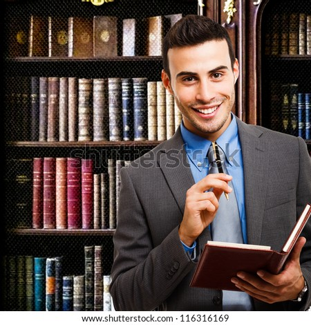 Portrait of a smiling businessman holding an agenda - stock photo