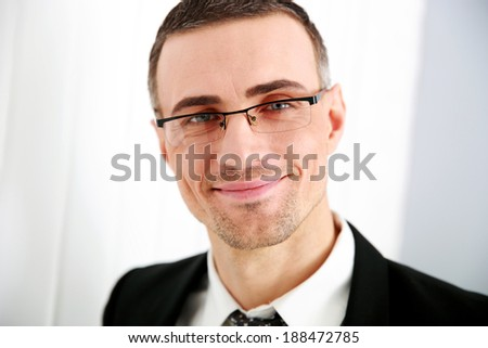 Portrait of a smiling businessman in glasses - stock photo