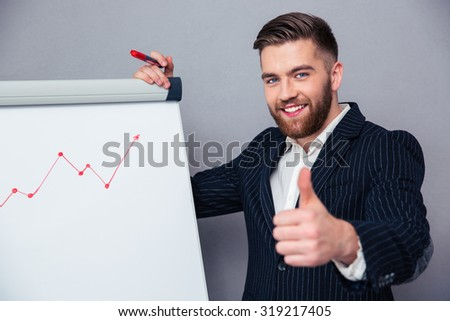Portrait of a smiling businessman presenting something on board and showing thumb up over gray background - stock photo