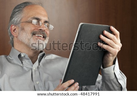 Portrait of a smiling businessman reading information from an electronic tablet. Horizontal shot. - stock photo