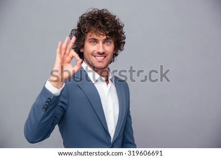 Portrait of a smiling businessman showing ok sign over gray background - stock photo