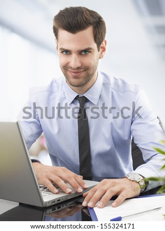 Portrait of a smiling businessman sitting in office with laptop