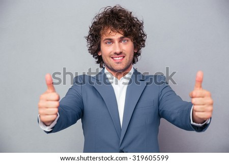 Portrait of a smiling businessman standing with thumbs up isolated on a white background - stock photo