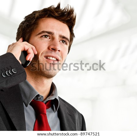 Portrait of a smiling businessman using a cellphone - stock photo