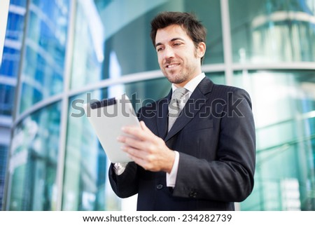 Portrait of a smiling businessman using his tablet computer - stock photo