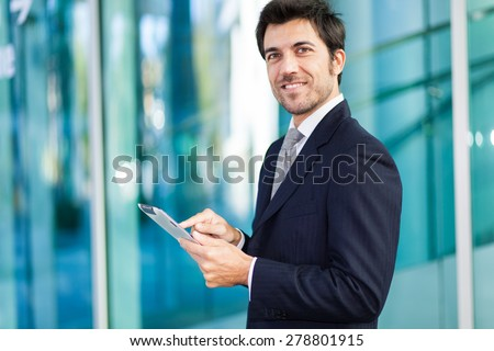Portrait of a smiling businessman using his tablet computer