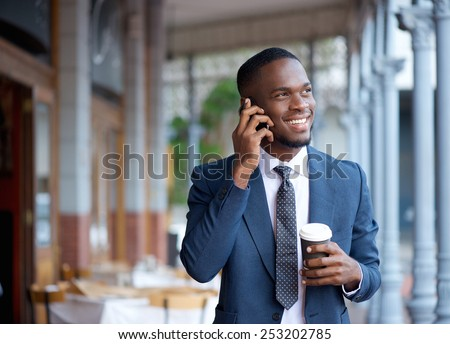 Portrait of a smiling businessman walking and talking on mobile phone - stock photo