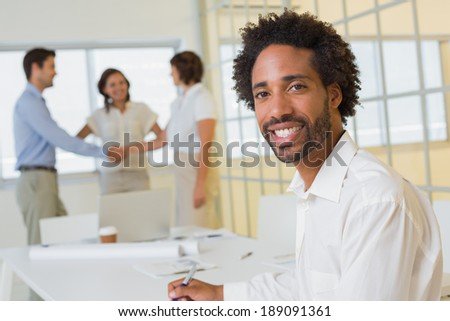 Portrait of a smiling businessman with colleagues hand shaking in background at the office - stock photo