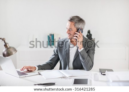 Portrait of a smiling businessman with grey hair and beard talking on his smartphone while he working on his computer while speaking, sitting in his office at his white desk wearing a grey suit. - stock photo