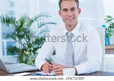 Portrait of a smiling businessman writing on a notebook - stock photo